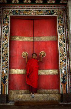 A Buddhist monk enters the formidable doors of Trongsa Dzong, Bumthang District, Bhutan √