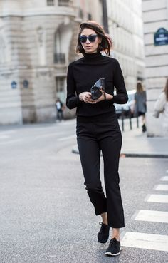 Shop this look on Lookastic: https://lookastic.com/women/looks/turtleneck-dress-pants-athletic-shoes-clutch-sunglasses/4896 — Navy Sunglasses — Black Turtleneck — Black Leather Clutch — Black Dress Pants — Black Athletic Shoes