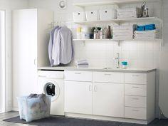 Eine Waschküche mit weissen Wandregalen, Unterschränken mit Türen oder Schubladen und Hochschrank mit Regalfächern