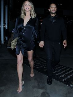 Chrissy Teigen wears Ann Demeulemeester Belted Satin Tunic and Yeezy Season 2 Lucite Heel