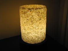 Luminária cilíndrica (28x36 cm) Superfície musiva realizada em técnica direta, utilizando pedras roladas semipreciosas (citrino e ônix) com acabamento misto (brilhante e opaco). Base em madeira com estrutura de acrílico e iluminação LED.