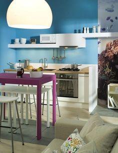 un mur bleu et des armoires blanches dans la petite cuisine sympa