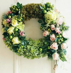 Secret Garden. Wrap moss around a Styrofoam wreath and insert greenery with hints of flowers - we love using pale pink roses as accents.