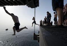 Sailors jump off aircraft elevator No. 4 during a swim call aboard the Nimitz-class aircraft carrier USS Carl Vinson (CVN 70).