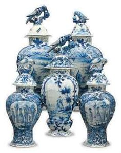 An assembled five piece Dutch Delft blue and white garniture of octagonal baluster vases and covers with 'parrot pecking fruit' finials, blue 'LPK' marks to the largest pair, blue 'W/899' mark to the single vase, late 18th/19th century.