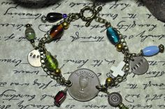 """This 7 1/2"""" bracelet contains one 1949 10 Prutah Israeli coin with a Howlite cross and glass multi color beads wire wrapped links and charm dangles. The curb link chain, findings and toggle clasp are antique bronze color. Two bronze round discs stamped """"Peace"""" & """"Faith"""" are also included."""