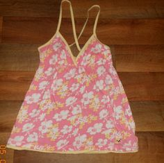 Hollister pink and yellow tank top Hollister criss cross tank top. Pink with yellow and white flowers. In good condition. Size small. Price firm. Listed on ebay at a lower price, please message if you would like the link. Also listed in tank top bundle. Hollister Tops Tank Tops
