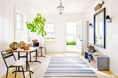 White walls, blue striped rug, grey bench, long wood table, and large black framed mirror