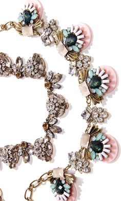 Art deco-inspired necklace with colorful stones and gold-toned metal. Includes an adjustable clasp closure.