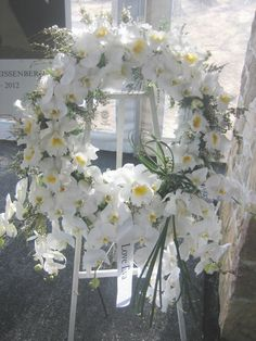 A striking memorial wreath designed with white Phalenopsis and Cataleya orchids by Buttercup.