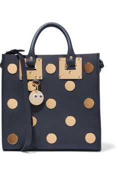 Sophie Hulme's 'Albion Square' tote is playfully embellished with gold metal polka-dots that will retain their glossy shine even after repeated wear. This structured navy leather style has a zipped pocket for your valuables, and can be held by the handles or an optional shoulder strap. It comes with a cute googly eye charm that can be attached to the front or to a wallet.