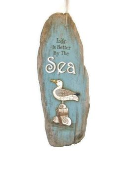 Hand painted driftwood sign. Ive painted this Seagull on driftwood with the saying Life is Better By The Sea. This is a rustic piece of driftwood that measures 22 > 9 and is kind of thick and chippy! Great addition to your beach cottage or just to add a beach, ocean atmosphere to any area. I DO combine shipping but due to the variety of sizes and weights of the items I have to offer, I do not specify a price in the listing. Please convo me for a price quote before you buy… or make your…