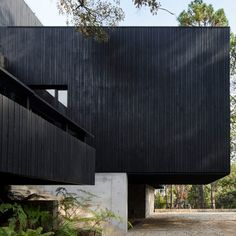 """Cedar charred black using the Japanese method of yakisugi and stone from a quarry in nearby Acatlán are used to blend this house """"as a shadow in the green surroundings"""".  Among the key features of the property is a huge cantilevered volume fronted by a large window that offers views from the living room to a nearby lake. Houses Architecture, Residential Architecture, Jacuzzi, Les Accents, Basement Floor Plans, Mug Design, Charred Wood, Dark House, Exposed Concrete"""