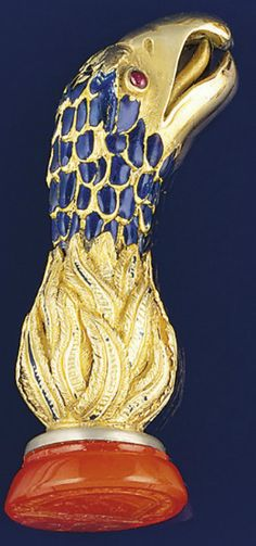 A 19th century gold, enamel and cornelian desk seal  The handle modelled as the head of an eagle with cabochon ruby eyes and blue enamel and engraved detail, the oval cornelian seal matrix engraved with armorial with the motto 'Though not the cat but a glove,' circa 1890.  Image Christies