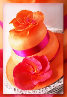 Orange cake with a pink flower on the side and an orange flower on the top