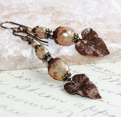 Leaf earrings with Czech glass fire polished faceted beads in crystal opal with a lovely, mottled metallic silver Picasso finish all over the bead. These opal glass earrings have a Vintaj brass woodland leaf charm that is beautifully detailed. The beads are separated by Vintaj