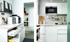 Büroräume mit weißer Arbeitsfläche und Schubladen. Darauf ein Drucker und Schreibtischorganisation. Daneben eine Teeküche mit Mikrowelle und ein paar Schneidebrettern.