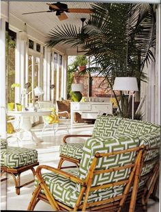 Cane furniture with green and white cushions, lamps, painted vj ceiling screened in, palms and plantation style fans