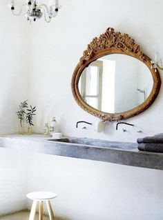 crazy about the mix of sleek and ornate in this bathroom....LOVE that mirror!