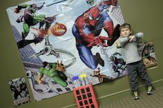 "superhero birthday party tip #6: Get a really big, really cheap superhero poster at a party store, grab a bunch of silly string, and have kids shoot webs at the bad guys. KIDS WENT NUTS.  Other games: ""Test Your Super Aim"": We wrapped a big cardboard box like a building + cut holes to make windows. Then we rigged it so that when you threw a ball into a window, it would come out a hole at the bottom of the box. ALSO: a coloring station, and enough loose balloons to keep them entertained for…"