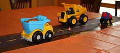 Construction paper table runner for trucks containing snacks (construction themed toddler birthday party).