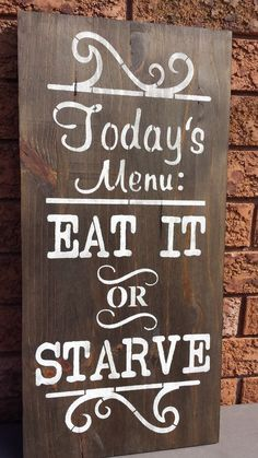 """KITCHEN SIGN/EAT OR STARVE MENU SIGN/HUMOROUS SIGNS/GAG GIFT/HOUSEWARMING GIFT/MOTHERS DAY GIFT WOOD SIGN IN A DARK WALNUT STAIN AND WHITE PAINT WITH SEALANT ADDED. CLAW TOOTH HANGER IS INSTALLED. MEASUREMENTS: 24"""" X 11 1/2""""  3/4"""" THICK CONTACT: kimbercreations@outlook.com Dark Walnut Stain, Kitchen Signs, Garden Fencing, Gag Gifts, White Paints, Funny Signs, Mother Gifts, House Warming, Wood Signs"""