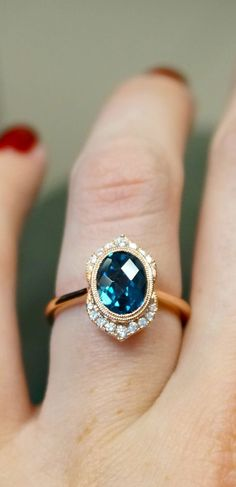 This stunning engagement ring by Joseph Jewelry features an oval London blue topaz bezel set in the center, surrounded by a double ring of milgrain beading and a modified halo of split prong set diamonds.