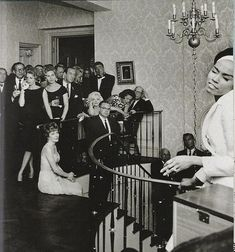 Here's one way we never picture her, as just another guest at a party. This fascinating snap shows Marilyn maybe an hour or so after singing Happy Birthday to JFK, watching Diahann Carroll perform at a townhouse on 69th Street. That's Jimmy Durante on the stairs    Photo by Cecil Stoughton  David Netto - The Notebook