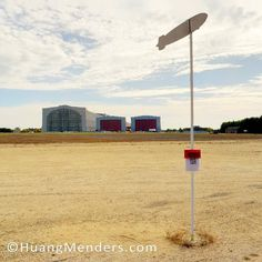 A post stands at the location of original mooring tower at the site of the Hindenburg zeppelin disaster. The Hindenburg Airship disaster at Lakehurst New Jersey on May 16 1937 brought an end to the age of the rigid airship. The Hindenburg's enormous hangar visible in the distance is still in use at the Joint Base McGuire-Dix-Lakehurst. #hindenburg #zeppelin #blimp #JointBaseMcGuireDixLakehurst #CathedralOfTheAir #blimpflood #aberdeenprovingground #runawayblimp #PrincetonPhotographer…