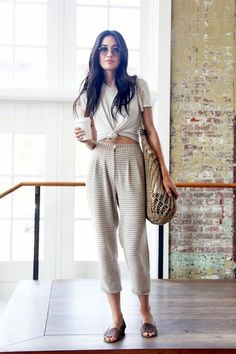 Model Jessica Mau wears a cropped knotted t-shirt, striped pleated pants, flat sandals, and round sunglasses.