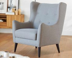Dania - A modern take on a traditional wingback chair, the Kamma chair features a dramatic profile, button-tufting and tapered wooden legs.