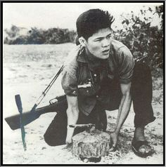 A Viet Cong fighter, his Chinese-made Type 53 rifle slung over his back, buries a landmine for a staged propaganda photo, 1964.