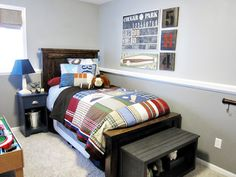 Gray boy room with plaid quilt and baseball bat hooks