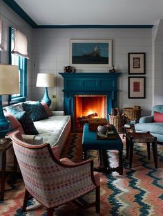 a teal fireplace is a natural solution for a coastal living room and other teal items echo with it perfectly creating a cohesive look Vintage Fireplace, Faux Fireplace, Fireplace Surrounds, Fireplace Design, Fireplaces, Minimalist Fireplace, Monochromatic Room, Colourful Living Room, Traditional Fireplace