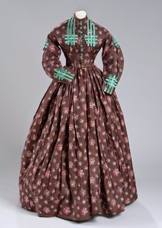Dark brown dress with separate skirt and bodice. Brown fabric is printed silk with a small floral decoration. Full skirt that shows signs of being taken out at one time and readjusted. Skirt is accompanied by two bodices.