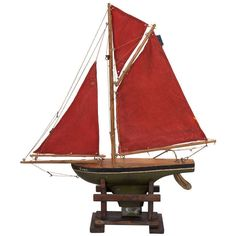 Circa 1900 wooden pond boat has a green rudder, brass fittings, wood deck and three red sails.