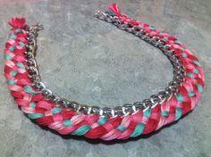 Collar de cadena color plata con tejido en hilos con tonalidades rosas con verde.