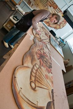 Object conservation technician, Anne Hinebaugh working to conserve the Leroy Flint mural from Woodhill Homes Estate Community Center