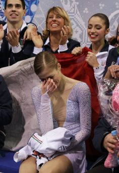"Carolina Kostner of Italy reacts in the ""kiss and cry"" area with her teammates during the Team Ladies Short Program at the Sochi 2014 Winter..."