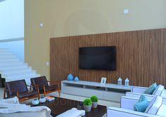 Um aparador executado sob medida em madeira laqueada branca abriga os aparelhos de áudio do home-theater, enquanto outro móvel em cumaru serve de apoio para a coleção de cristais turquesa da proprietária.