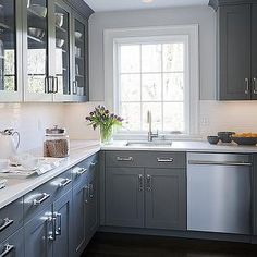 Kitchens by Deane - kitchens - gray kitchens, gray kitchen cabinets, gray cabinets, gray walls, glass-front cabinets, glass-front kitchen cabinets, glass front upper cabinets, white marble, white marble countertops, blanco sinks, stainless steel dishwasher, dishwasher next to sink vintage glass canisters, hardwood floors,