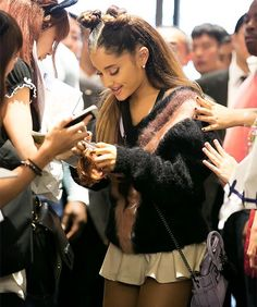 Ariana grande using her phone in front of fans.:).