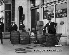 Prohibition officers seizing liquor from a speakeasy. 1920s.