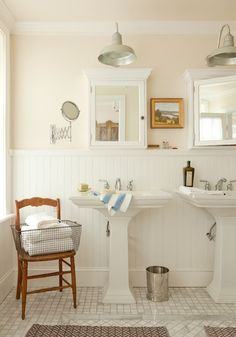Chair with basket of towels . .   Lovely pink bathroom with pale pink walls paint color, chair rail & beadboard, glossy white pedestal sinks, white medicine cabinets, marble mosaic square tiles floor and herringbone bath mats.