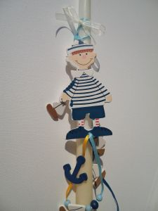 Greek Easter candle (lambada) for kids decorated with a wooden sailor boy, anchors and boats.