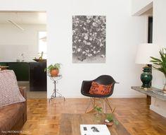 Sala de estar integrada à cozinha. Na decoração a moradora optou pelo uso de cores como marrom, ocre e verde.