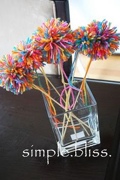 """yarn pop poms or wands tutorial. also seen these made the same way with silver metallic twine as """"sparklers"""" very cute & easy"""