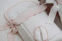 Close up del saquito de invierno para el cuco en piqué blanco y bodoques rosas
