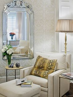Pops of brassy gold in the nailhead trim on the cushioned armchair, the snakeskin-print pillow and brass floor lamp add visual depth to this master bedroom sitting area. A Venetian mirror adds a touch of traditional elegance.