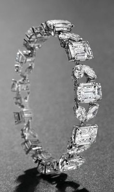 A MAGNIFICENT DIAMOND BRACELET, BY VAN CLEEF & ARPELS Set with eleven rectangular-cut diamonds, weighing approximately 5.71 to 2.72 carats, interspersed by twin marquise-shaped diamond links, 1966, 17.0 cm, with French assay marks for platinum and gold Signed Van Cleef & Arpels, no. 9.324CS
